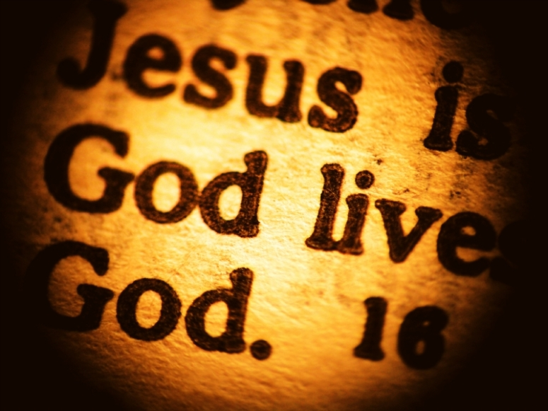 A macro look at a New Testament biblical passage focusing on the words Jesus and God forming the central message of Christianity. Warm sepia tone.